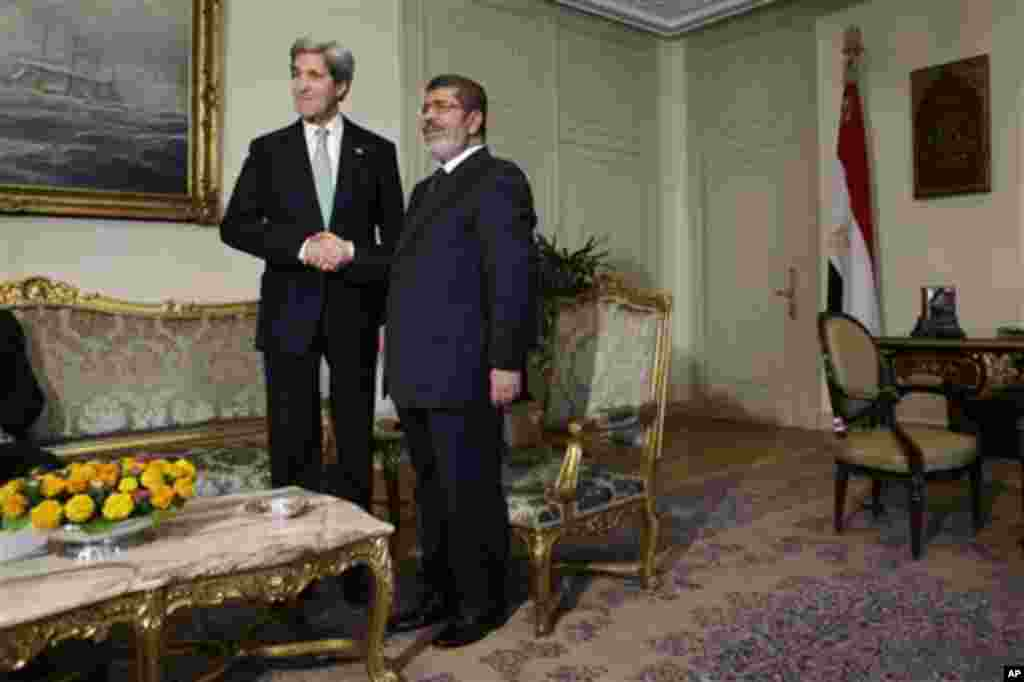 U.S. Secretary of State John Kerry, left, shakes hands with Egyptian President Mohamed Morsi at the Presidential Palace in Cairo, Egypt on Sunday, March 3, 2013. U.S. Secretary of State John Kerry met with Egypt's president Sunday, wrapping up a visit to