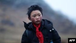 """8岁的云南""""冰花男孩""""王福满(2018年1月11日)。云南山区鲁甸的8岁小学生王福满身穿单薄的衣服攀爬山路走到学校,头发上结满了白白冰花的照片,让无数网友心碎和震惊。"""