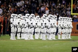 "Stormtroopers line up on the field during an NFL football game between the Chicago Bears and the Minnesota Vikings, Oct. 9, 2017, in Chicago. The trailer for ""Star Wars: The Last Jedi"" debuted during halftime."