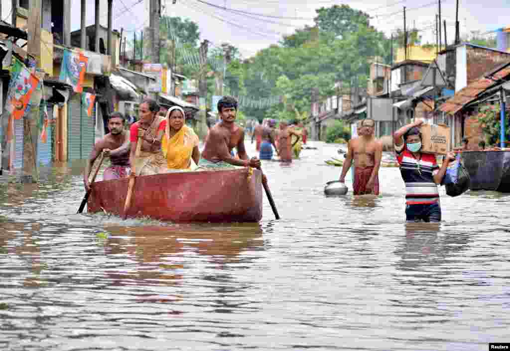 People wade through a flooded street to collect food and drinking water from a distribution center in Amta town of Howrah district in the eastern state of West Bengal, India.