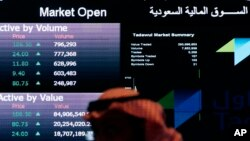 FILE - A Saudi man looks at stocks at the Tadawul Saudi Stock Exchange, in Riyadh, Saudi Arabia.
