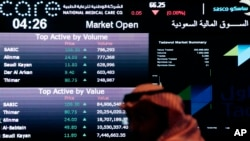 FILE - A Saudi man looks at stocks at the Tadawul Saudi Stock Exchange, in Riyadh, Saudi Arabia, June 15, 2015.