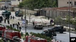 Pasukan keamanan Afghanistan dan petugas tanggap darurat berkumpul di depan kompleks parlemen yang diserang Taliban di Kabul (22/6). (AP/Rahmat Gul)
