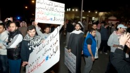 Demonstrators carry placards during a protest in Kuwait City, January 6, 2013.