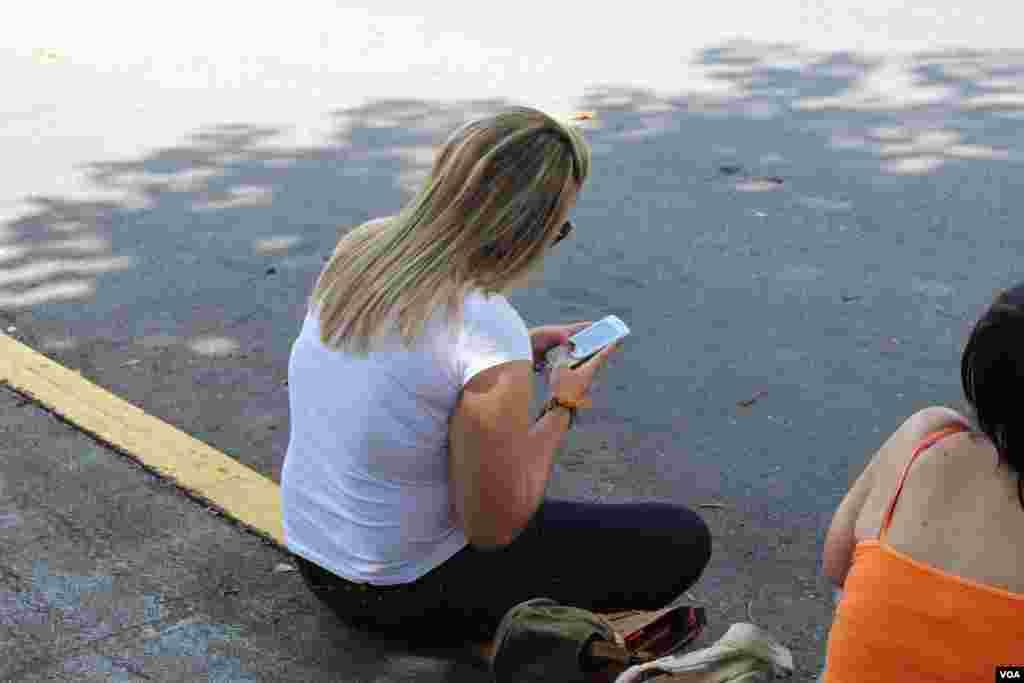 Una mujer envía un texto después de emitir su voto para elegir al nuevo presidente venezolano, el domingo 7 de octubre. [Foto: Iscar Blanco, VOA]