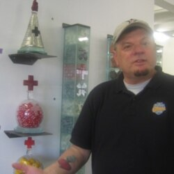 Tim Tate in front of several of his glass artworks