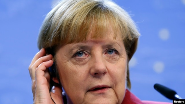Germany's Chancellor Angela Merkel adjusts her headset during a news conference at a European Union leaders summit in Brussels Oct. 25, 2013.