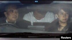 Кацуя Такахаси (на заднем сидении полицейской машины)