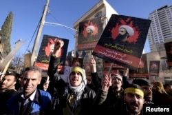 Iranian protesters chant slogans as they hold pictures of Shi'ite cleric Sheikh Nimr al-Nimr during a demonstration against the execution of Nimr in Saudi Arabia, outside the Saudi Arabian Embassy in Tehran Jan. 3, 2016