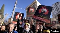 Demonstran Iran meneriakkan slogan sambil membawa foto ulama Syiah Sheikh Nimr al-Nimr saat demo menentang eksekusinya di Saudi Arabia, di luar Kedutaan Besar Arab Saudi di Teheran 3 Januari 2016.