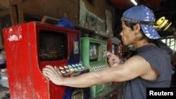 Penambang emas di Filipina bermain permainan komputer sebelum masuk ke terowongan untuk menambang di Diwalwal, Filipina selatan. (Foto: Reuters/Erik De Castro)