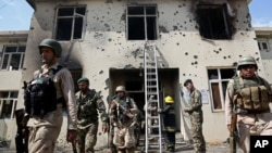 Afghan security personal surround the area after Taliban fighters stormed a government building in Jalalabad, east of Kabul, May 12, 2014.