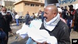 Wani dan kasar Libya yake dauke da bangaren jikin wani a asibitin Jalala dake kasar.