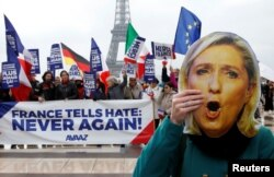 "FILE - A person holds a mask of France's National Front (FN) defeated presidential candidate, Marine Le Pen, as people gather with French and European flags near the Eiffel Tower and a banner with the message, ""France tells Hate: Never Again """