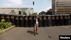 Seorang pria menggunakan ponsel dalam aksi massa menyusul penetapan hasil pilpres. Aksi masa berlangsung dekat kantor Badan Pengawas Pemilihan Umum (Bawaslu) di Jakarta, Indonesia, 22 Mei 2019. (Foto: Reuters/Willy Kurniawan)