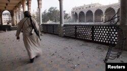 Một chiến binh phe nổi dậy trong đền thờ Khalid ibn al-Walid, bị hư hại vì giao tranh