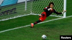 Mexico's Guillermo Ochoa goes the wrong way as Klaas-Jan Huntelaar (unseen) of the Netherlands scores on a decisive penalty kick at the Castelao arena in Fortaleza, June 29, 2014.