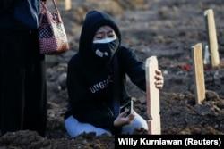Seorang gadis berduka usai pemakaman ayahnya yang berusia 56 tahun yang meninggal karena COVID-19, di area pemakaman yang disediakan pemerintah untuk korban COVID-19, di Jakarta, 28 Juni 2021.(Foto: REUTERS/ Willy Kurniawan)