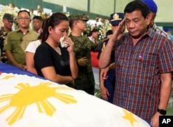 FILE - Philippine President Duterte salutes flag-draped coffins of 15 soldiers killed in a gun battle with Muslim Abu Sayyaf militants during his visit to Western Mindanao Command in Zamboanga city, southern Philippines, Aug. 31, 2016
