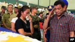 Presiden Filipina Rodrigo Duterte memberi hormat ke arah peti jenazah 15 tentara yang tewas dalam pertempuran dengan militan Abu Sayyaf di kota Zamboanga, Filipina selatan, Agustus 2016.