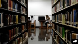 FILE - Students are seen studying in a library on the campus of California State University in Long Beach, California, Oct. 19, 2012. After factoring in age, gender, education and economic status, researchers found that readers lived two years longer than non-readers.