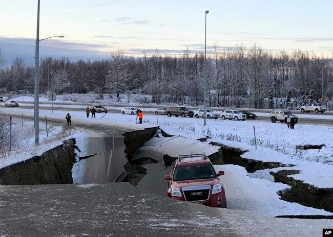Un auto queda atrapado en una sección colapsada de la rampa de salida de Minnesota Drive en Anchorage, el viernes 30 de noviembre de 2018.