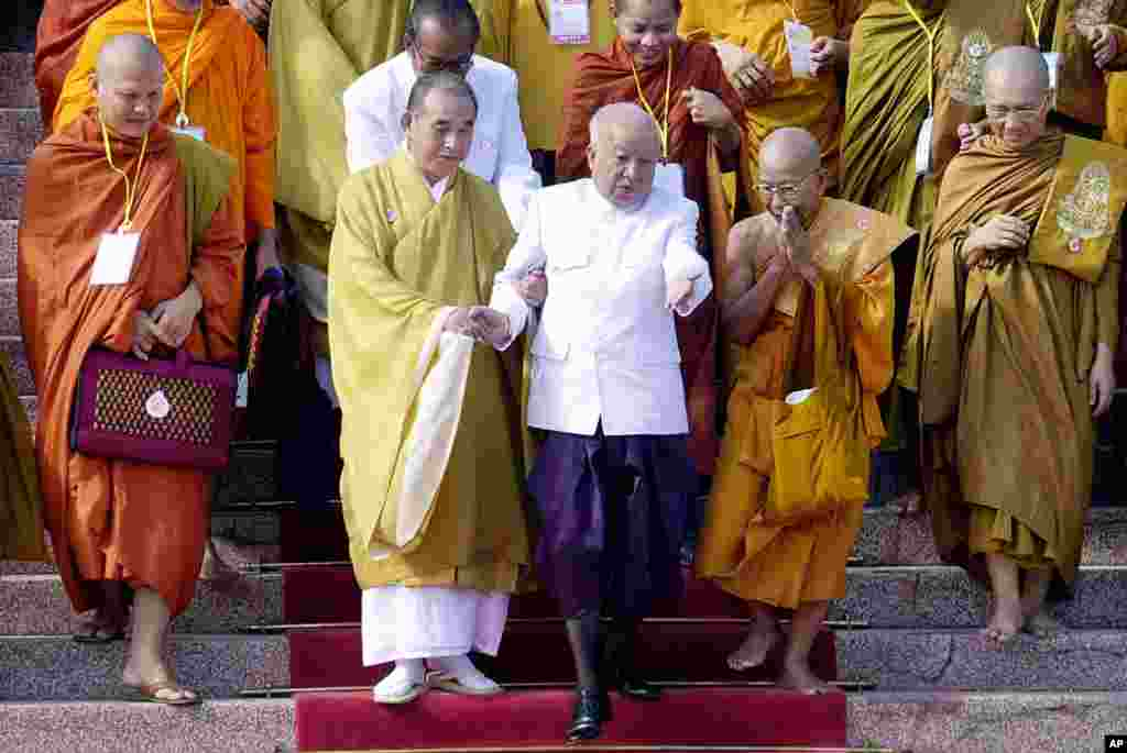 Then King Sihanouk, center, is helped down stairs at the Royal Palace in Phnom Penh, with help from Buddhist leaders attending the opening ceremonies of the World Buddhist Conference, December 5, 2002.