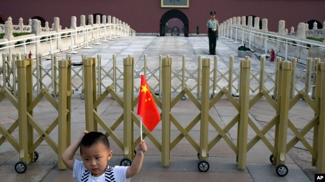 A child holds up a Chinese national flag as he poses for a photo in front of Tiananmen Gate in Beijing, June 4, 2014.