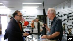 FILE - Sales associate Mike Conway, right, shows Paul Angulo a semiautomatic rifle at Bullseye Sport gun shop in Riverside, Calif., Dec. 9, 2015. Guns can be bought online without a background check.