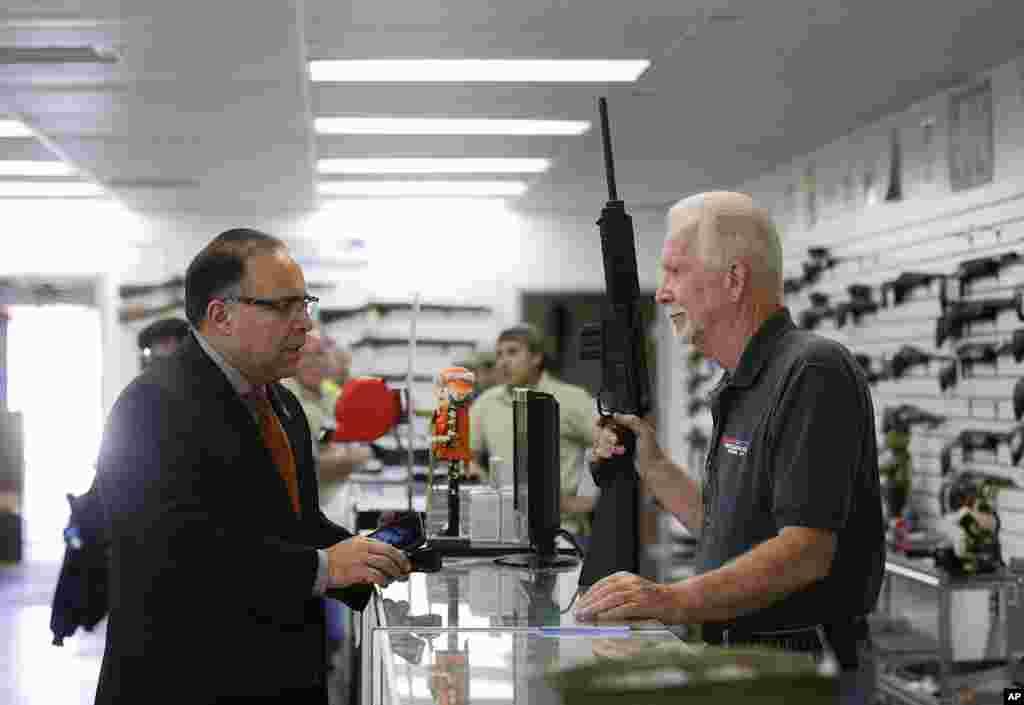 Un vendeur de chez Bullseye Sport montre une armesemi-automatique à un client à Riverside en Californie, le 9 décembre 2015.