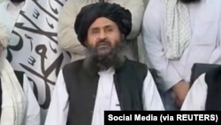 Mullah Baradar Akhund, a senior official of the Taliban, seated with a group of men, makes a video statement, in this still image taken from a video recorded in an unidentified location and released on August 16, 2021. Social Media/via REUTERS THIS IMAGE HAS BEEN SUPPLIED BY A