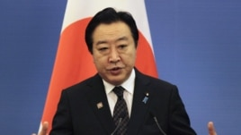 Japan's Prime Minister Yoshihiko Noda gestures in front of a Japanese national flag as he speaks at a joint news conference, May 13, 2012.