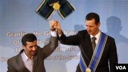 Presiden Iran Mahmoud Ahmadinejad mengangkat tangan Presiden Suriah Bashar al-Assad seusai upacara penganugerahan medali kehormatan di Teheran, Iran hari ini.