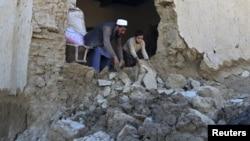 阿富汗楠格哈尔省灾区的一名男子和他的儿子清理在地震中毁坏的房屋。(2015年10月27日)