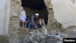 Un hombre y su hijo limpian su casa dañada por el terremoto del lunes, en el distrito Behsud de la provincia Nangarhar, en Afganistán.