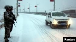 2017年12月27日,中國新疆維吾爾自治區阿勒泰市,中國軍人在大雪中站崗,确保交通安全。
