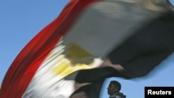 A man carries an Egyptian flag near Cairo's Tahrir Square where demonstrators are gathering to mark the first anniversary of Egypt's uprising, January 25, 2012.