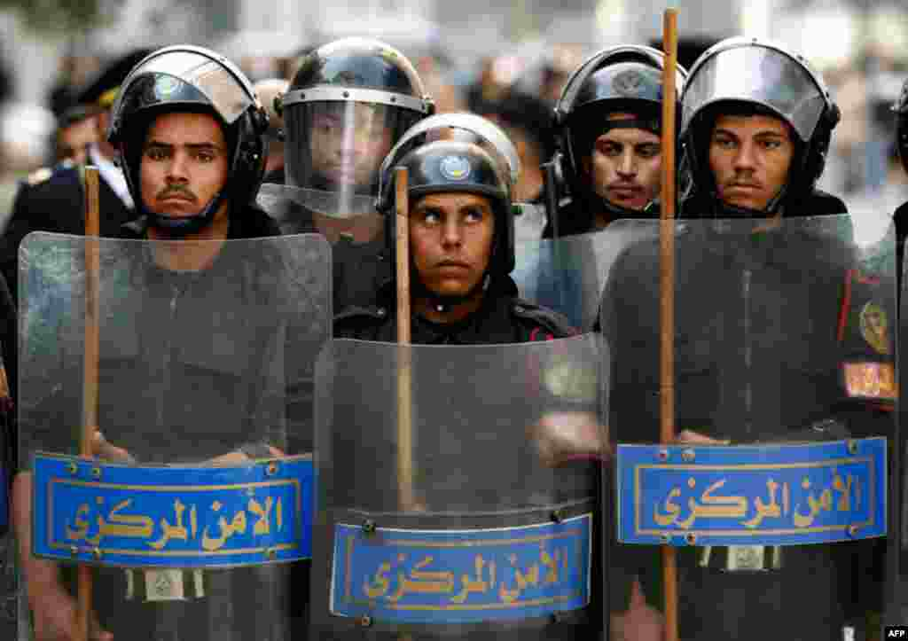 January 26: Riot police keep watch as they hold shields during clashes with protesters in Cairo. Thousands of Egyptians defied a ban on protests by returning to Egypt's streets on Wednesday and calling for President Hosni Mubarak to leave office, and some