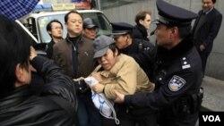 Un manifestante es arrestado por la policía cerca de un sitio donde iba a realizarse una protesta, en la Plaza Shaghai.