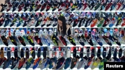 FILE - A customer shops for shoes at a mall in Hefei, Anhui province, China, March 10, 2015.