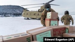 In this photo provided by the Alaska National Guard, soldiers from 1st Battalion, 207th Aviation Regiment, unload gifts from a CH-47 Chinook helicopter in Nanwalek, Alaska, during Operation Santa Claus, on Dec. 11, 2020.
