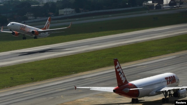 Brazilian airline GOL's Boeing 737-800 aircraft, left, takes off near TAM's Airbus A320 aircraft at Congonhas airport, Sao Paulo, Jan. 17, 2014.
