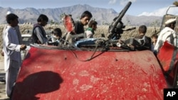 Afghans are seen around wreckage of a civilian car, which was hit by a roadside bomb in Laghman, east of Kabul, Afghanistan.