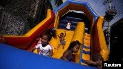 """تصویری کودکان برزیلی که در یک """"قلعه بادی"""" بازی می کنند."""