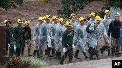 Rescatistas caminan hacia la entrada de una cueva donde permanecen atrapados un niño y su entrenador de fútbol en Mae Sai, en la provincia de Chiang Rai, norte de Tailandia, el martes, 10 de julio de 2018.