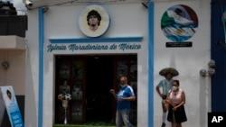 Turis berfoto di depan Gereja Maradona di San Andres Cholula, negara bagian Puebla, Meksiko, Minggu, 18 Juli 2021. (AP Photo/Marco Ugarte)