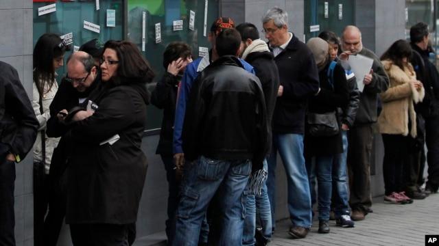 People wait outside an unemployment office in Madrid, Spain, Apr. 2, 2013.