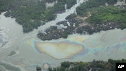FILE -Oil is seen on the creek water's surface near an illegal oil refinery in Ogoniland, outside Port Harcourt, in Nigeria's Delta region, March 24, 2011.