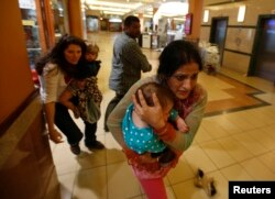 Women carrying children run for safety as armed police hunt for gunmen who went on a shooting spree in Westgate shopping center in Nairobi, Kenya, Sept. 21, 2013.