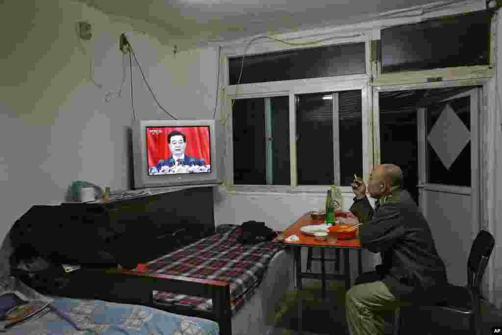 8일 제 18차 중국 공산당 전국대표대회 개막을 시청하고 있는 베이징 시민.